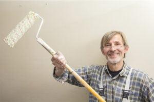 Senior mand holder sin malerbørste og smiler