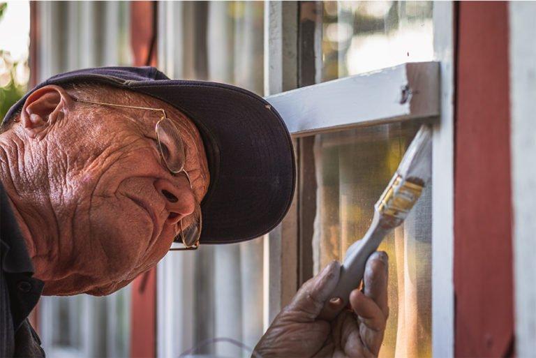 Koncentreret senior maler vinduer udendørs