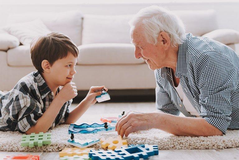 Pensionist spiller brætspil med barn