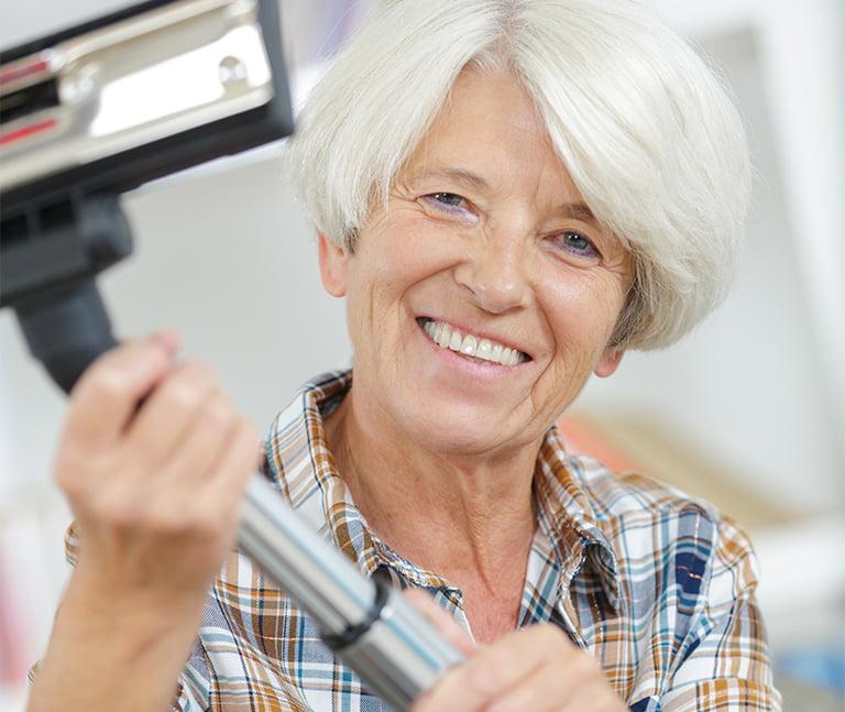 Glad bedstemor står med støvsuger