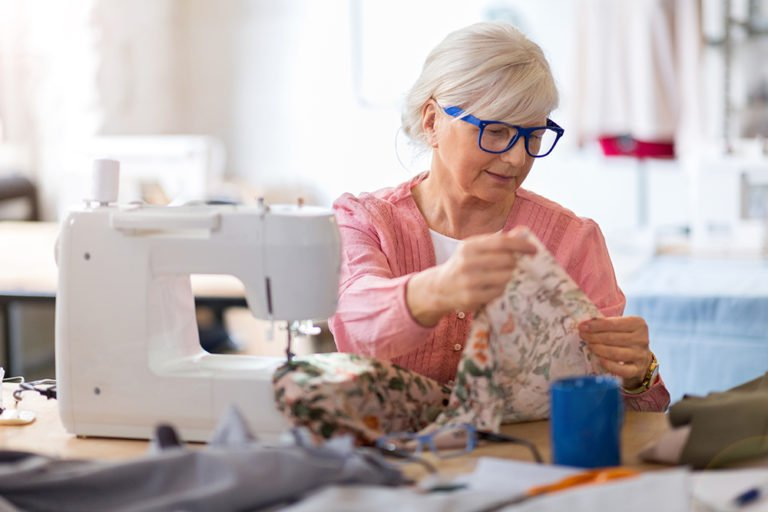 koncentreret senior arbejder på symaskine