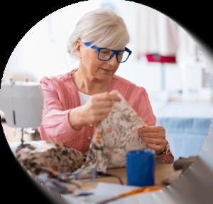Koncentreret bedstemor arbejder ved symaskine