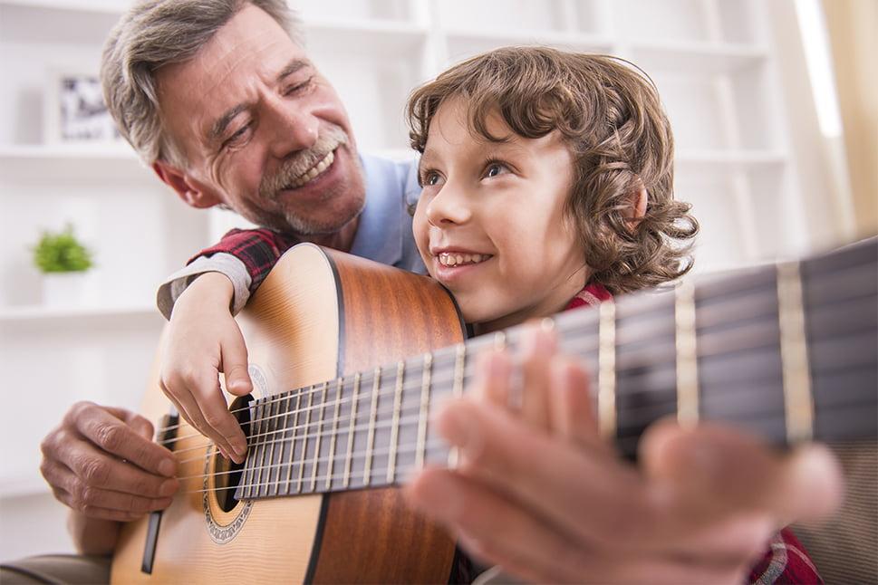 Glad senior underviser dreng på guitar