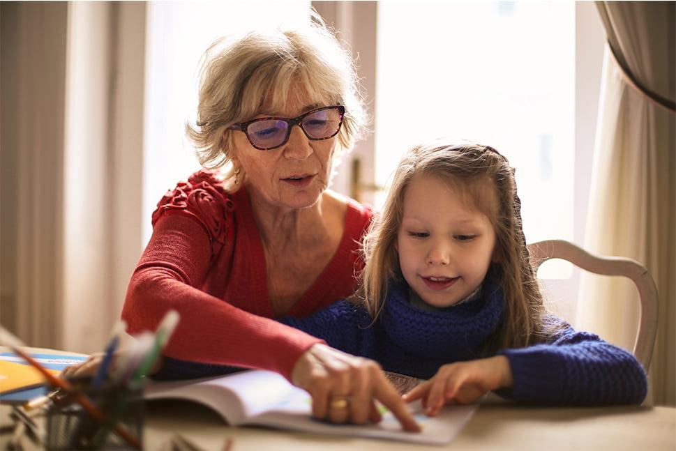 Sød bedstemor underviser pige, hjælper med lektier