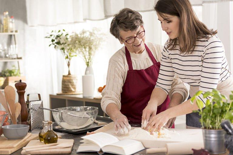 Sød senior underviser madlavning i køkkenet