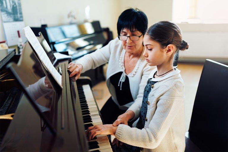 Koncentreret pige bliver undervist på klaver af en pensionist